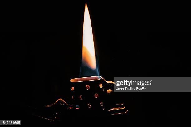 close-up of ignited cigarette lighter against black background - cigarette lighter stock pictures, royalty-free photos & images