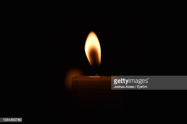 close-up of illuminated candle against black background - candle stock pictures, royalty-free photos & images