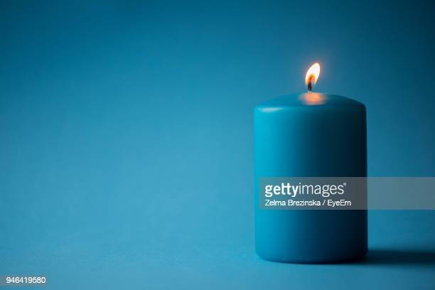 close-up of illuminated candle against blue background - candle stock pictures, royalty-free photos & images