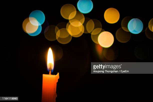 close-up of illuminated candle against lens flare - ローソク ストックフォトと画像