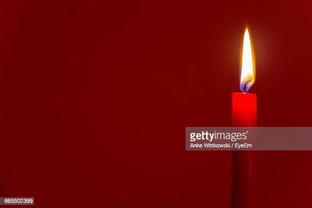 Close-Up Of Illuminated Candle Against Red Background