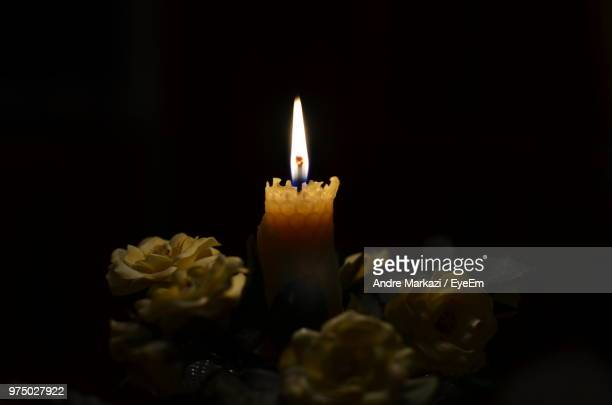 Close-Up Of Illuminated Candle By Flowers Against Black Background