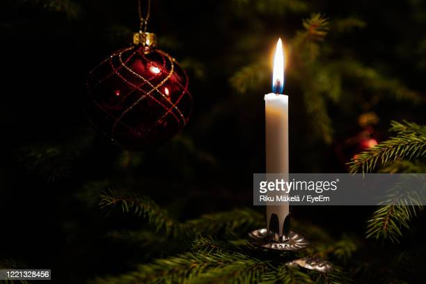 close-up of illuminated candle on christmas tree - christmas decore candle stock pictures, royalty-free photos & images
