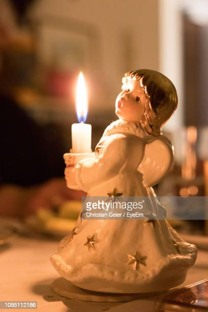 close-up of illuminated candle with figurine on table - human representation stock pictures, royalty-free photos & images