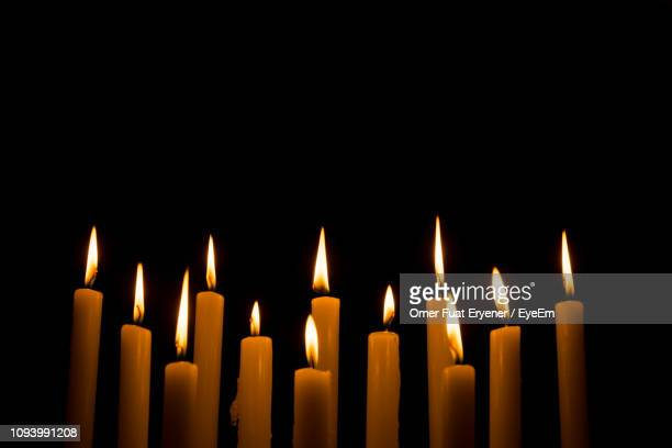 close-up of illuminated candles against black background - candlelight stock pictures, royalty-free photos & images