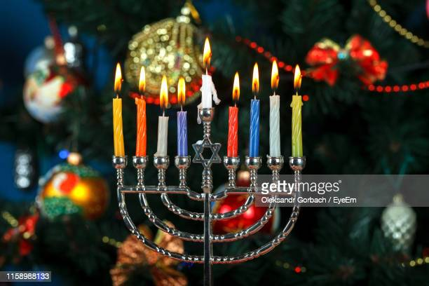 close-up of illuminated candles and christmas decorations - hanukkah imagens e fotografias de stock
