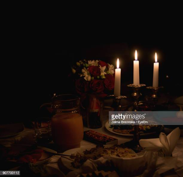Close-Up Of Illuminated Candles By Vase On Dining Table
