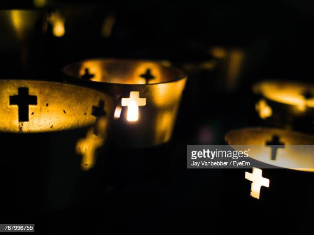 close-up of illuminated candles in church - kirche stock-fotos und bilder