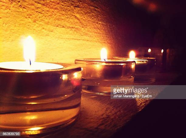 close-up of illuminated candles in glass holder against wall - cero foto e immagini stock