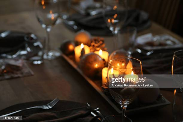 Close-Up Of Illuminated Candles On Dining Table