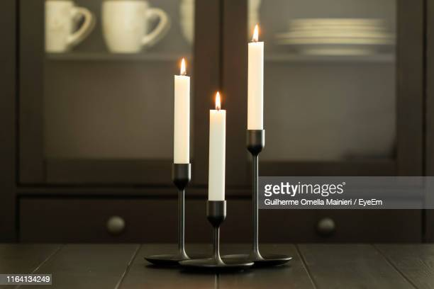 close-up of illuminated candles on table at home - candlestick holder stock pictures, royalty-free photos & images