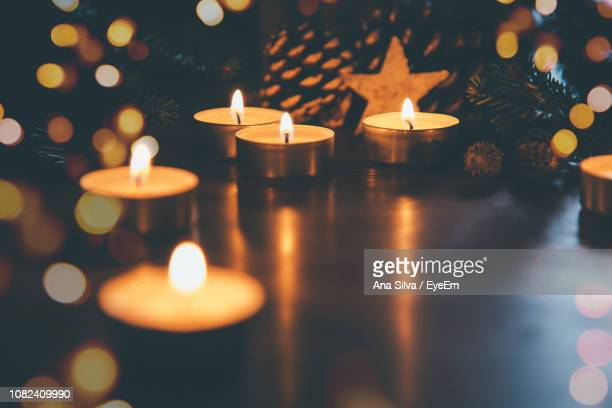 close-up of illuminated christmas lights on table at night - candle light stock pictures, royalty-free photos & images