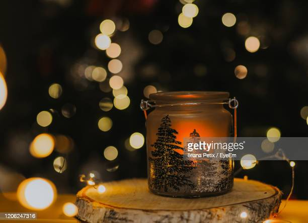 close-up of illuminated christmas lights on table - christmas decore candle stock pictures, royalty-free photos & images