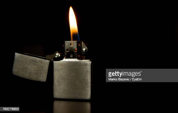 close-up of illuminated cigarette lighter over black background - cigarette lighter stock pictures, royalty-free photos & images