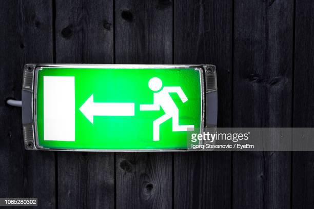 close-up of illuminated directional sign on wooden door - exit sign stock pictures, royalty-free photos & images