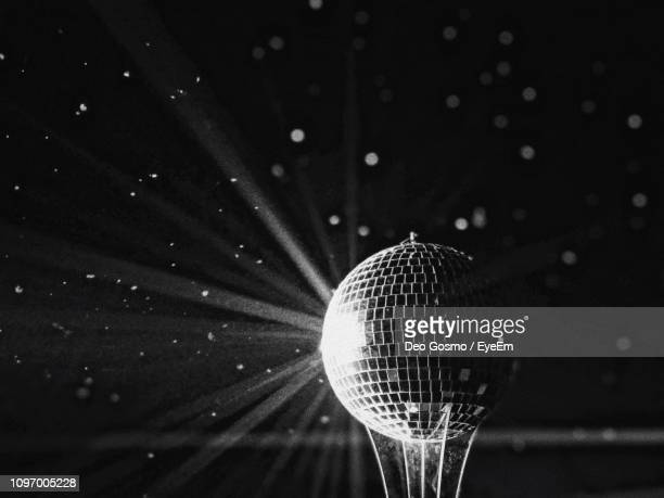 close-up of illuminated disco ball against black background - mirror ball stock pictures, royalty-free photos & images