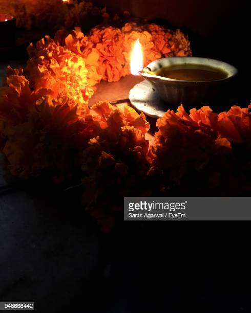 Close-Up Of Illuminated Diya Amidst Garland On Table