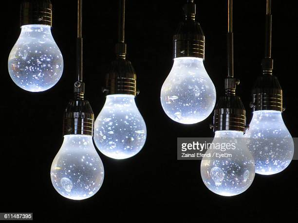 Close-Up Of Illuminated Electric Bulbs Against Black Background
