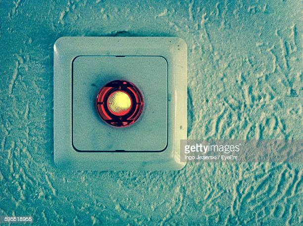 Close-Up Of Illuminated Emergency Button On Wall