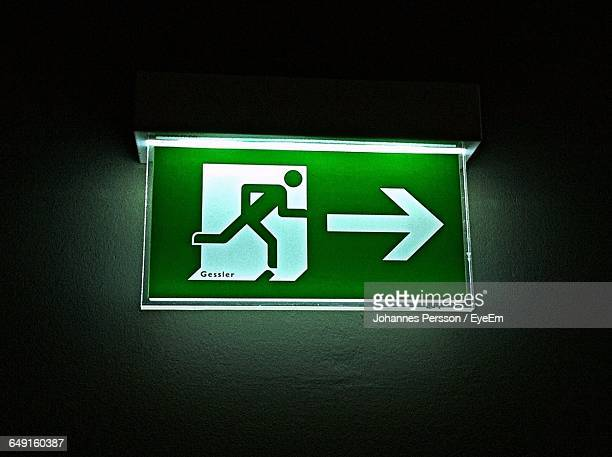 Close-Up Of Illuminated Emergency Exit Sign On Wall