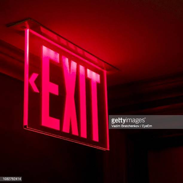 close-up of illuminated exit sign - exit sign stock pictures, royalty-free photos & images