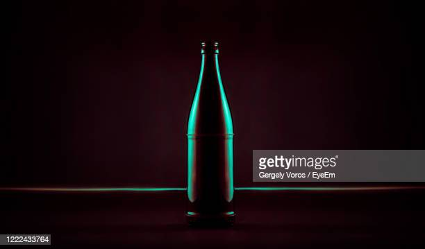 close-up of illuminated green beer bottle against black background - back lit stock pictures, royalty-free photos & images