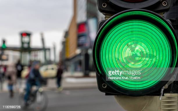 close-up of illuminated green light signal in city - stoplight stock pictures, royalty-free photos & images
