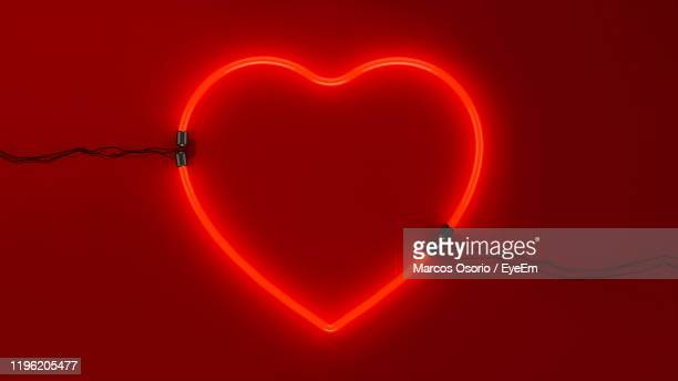 close-up of illuminated heart shape against black background - liefde stockfoto's en -beelden