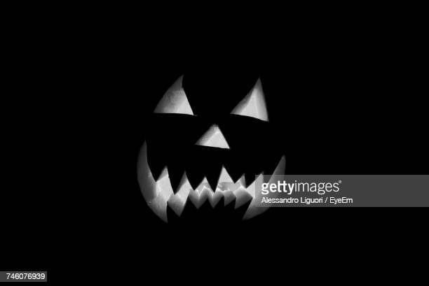 close-up of illuminated jack o lantern against black background - scary pumpkin faces stock photos and pictures