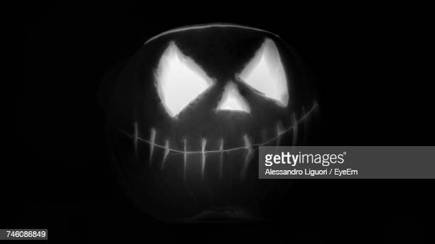 close-up of illuminated jack o lantern against black background - anthropomorphic face stock pictures, royalty-free photos & images