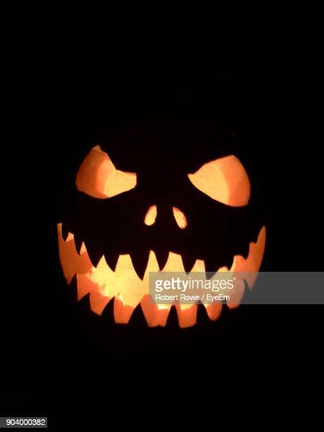 close-up of illuminated jack o lantern against black background - halloween lantern stock photos and pictures