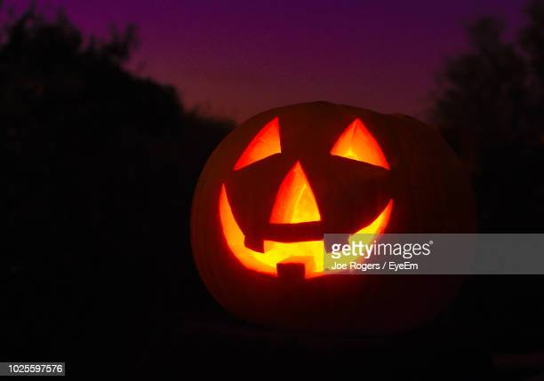 close-up of illuminated jack o lantern at night - halloween lantern stock photos and pictures