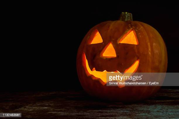 close-up of illuminated jack on lantern on table against black background - pumpkin stock pictures, royalty-free photos & images