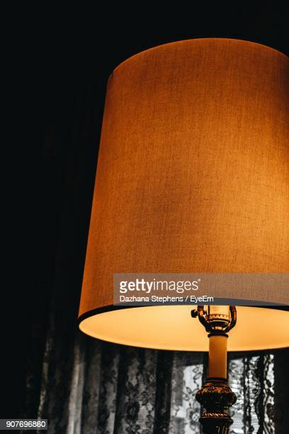 Close-Up Of Illuminated Lamp By Curtain In Darkroom