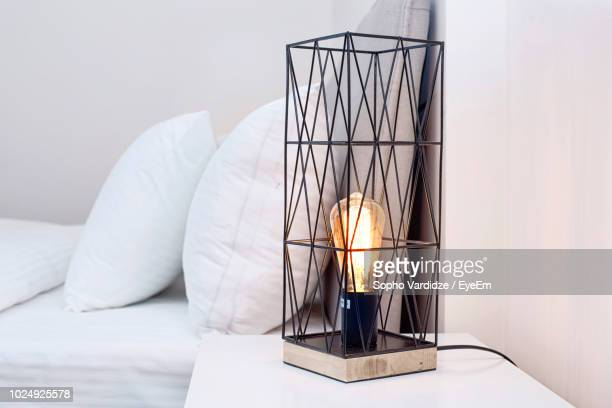 close-up of illuminated lamp on night table by bed at home - electric lamp stock pictures, royalty-free photos & images
