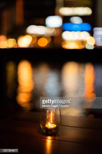 close-up of illuminated lamp on table at night - quayside stock pictures, royalty-free photos & images