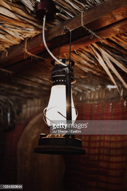 Close-Up Of Illuminated Lantern Hanging From Thatched Roof