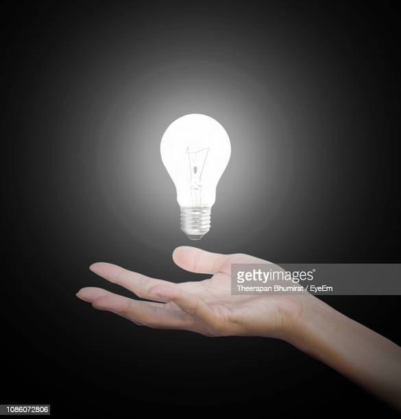 close-up of illuminated light bulb against black background - energy efficient lightbulb stock pictures, royalty-free photos & images