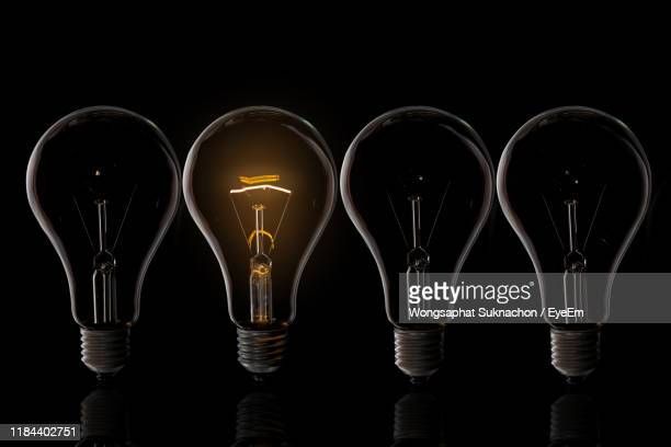 close-up of illuminated light bulb against black background - side by side stock pictures, royalty-free photos & images