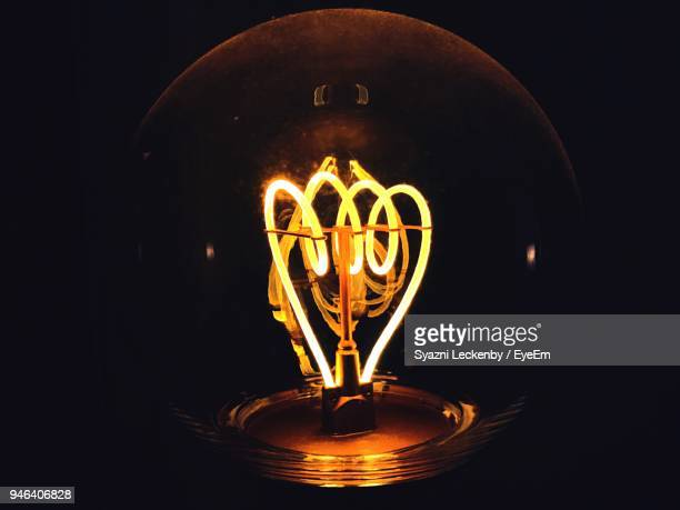 close-up of illuminated light bulb against black background - filament stock photos and pictures