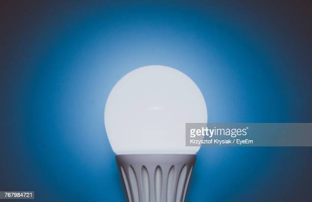 close-up of illuminated light bulb against blue background - energy efficient lightbulb stock photos and pictures