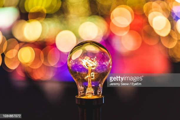 close-up of illuminated light bulb against bokeh - strom stock-fotos und bilder