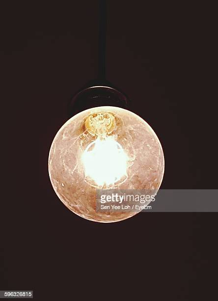 Close-Up Of Illuminated Light Bulb Against Colored Background