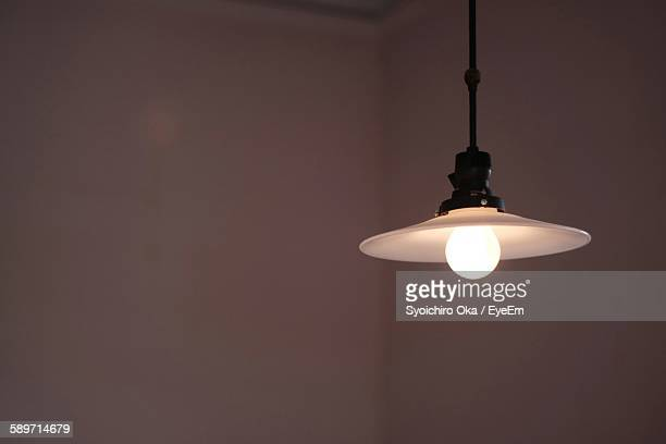 Close-Up Of Illuminated Light Bulb Against Wall