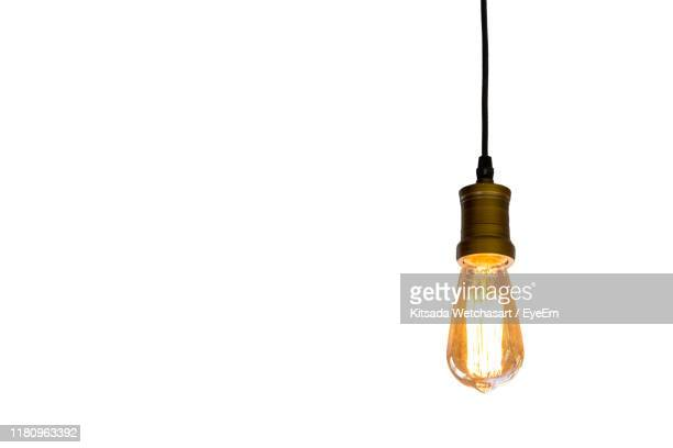 close-up of illuminated light bulb against white background - electric lamp stock pictures, royalty-free photos & images