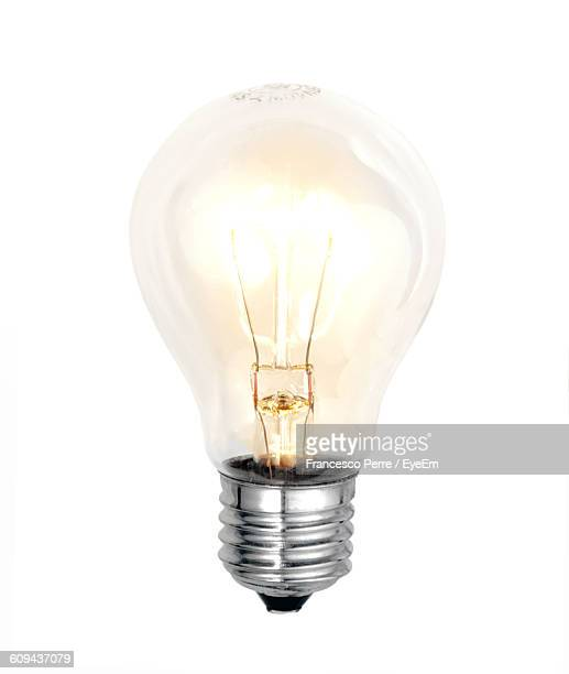 close-up of illuminated light bulb against white background - light bulb stock pictures, royalty-free photos & images