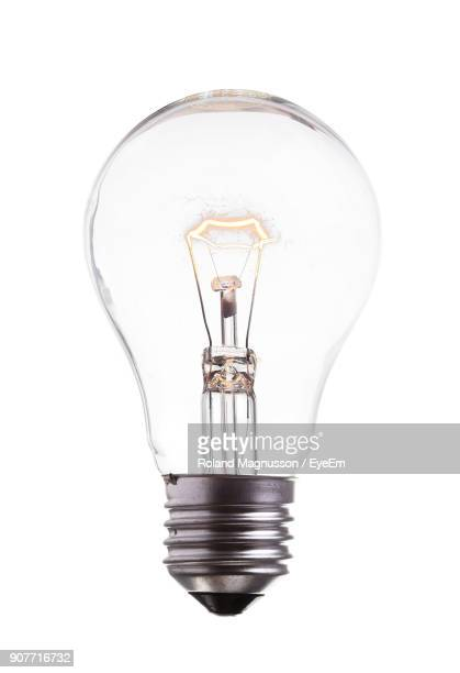 close-up of illuminated light bulb against white background - lâmpada elétrica - fotografias e filmes do acervo
