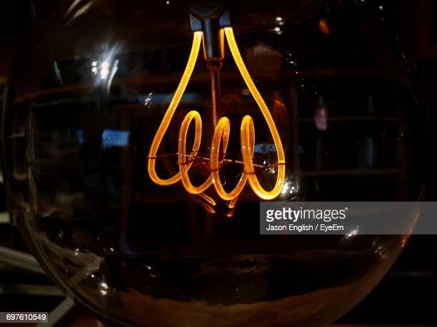 close-up of illuminated light bulb in darkroom - filament stock photos and pictures