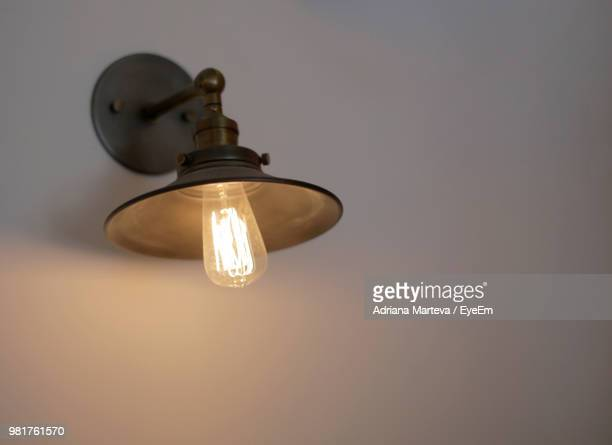 Close-Up Of Illuminated Light Bulb On White Wall
