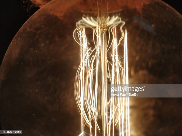 close-up of illuminated light bulb - energy efficient lightbulb stock photos and pictures